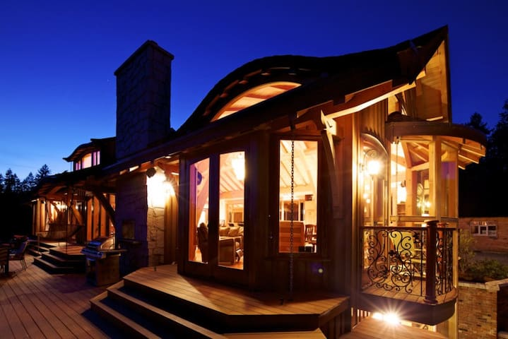 Evening Glimpse of the Front Deck. *Outdoor entertainment area includes; dinning table, lounging chairs, fire place, BBQ and hot tub.