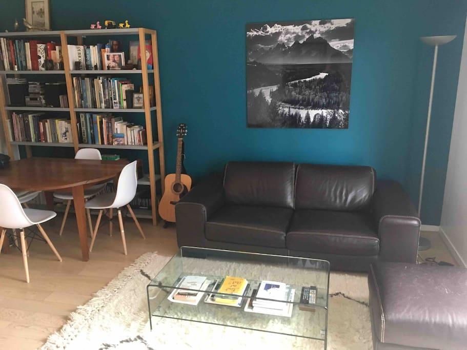 - A droite : Coin salon avec canapé et pouf en cuir, table basse en verre et tapis berbère. - A gauche : Coin salle à manger avec table ronde en bois et 4 chaises scandinaves.