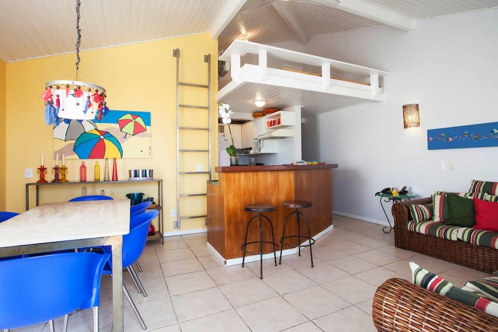 Visão da entrada da sala com cozinha e mezanino