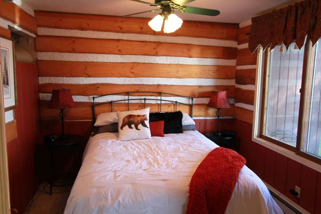 The bedroom has a rustic cabin feel and features a queen size bed.