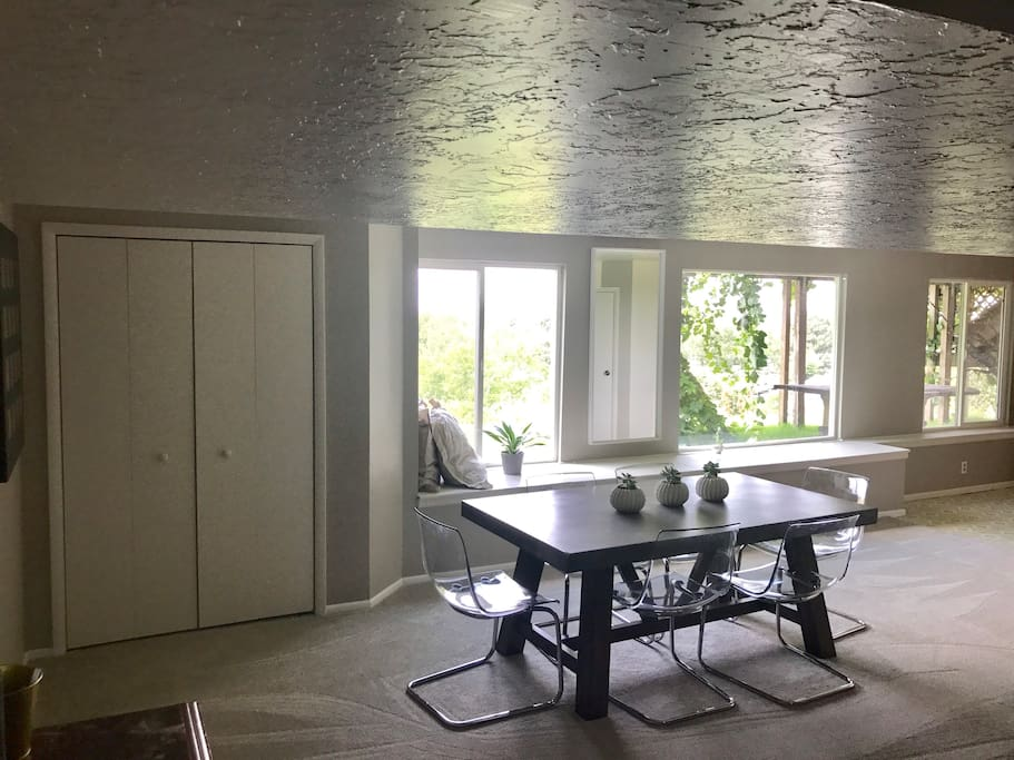 Dining room table looking out large West facing windows. Blackout shades over windows to block afternoon sun.