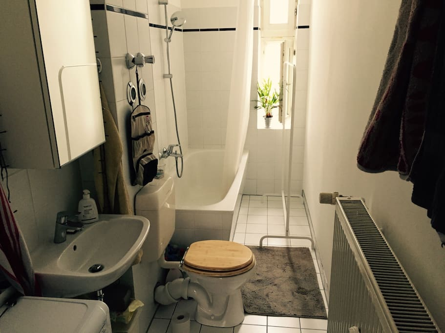 Bathroom with tube, daylight through windows and (not in the picture) a washing machine