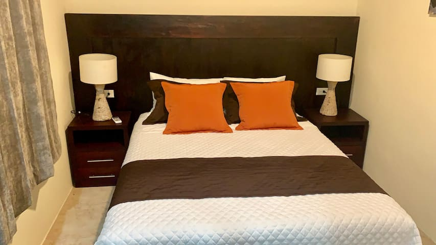 Master bedroom fitted with a qeen size bed. Custom made in Galapagos wooden headboard and night stands.