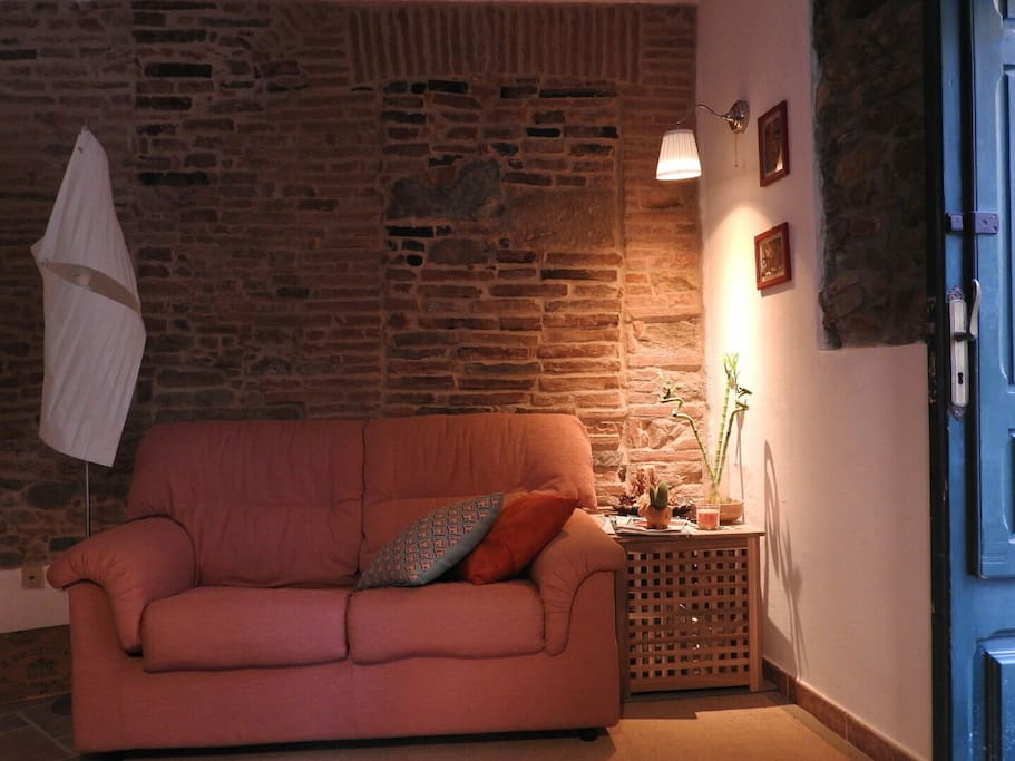 The living area  The room has a sofa-bed suitable for two children or one adult. Exposed stone and brick walls