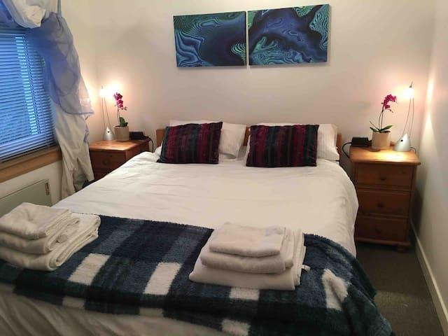 Master bedroom with Kingsize bed, at dusk.
