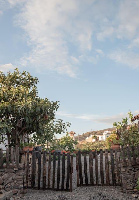 Verja hecha a partir de tablas de barrica que conduce a la parte trasera del jardín, donde se hallan un baño una zona techada y amueblada a modo de cocina y con chimenea y brasa.