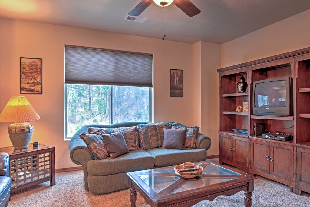 The open living space features comfortable furnishings and views of the surrounding forest.