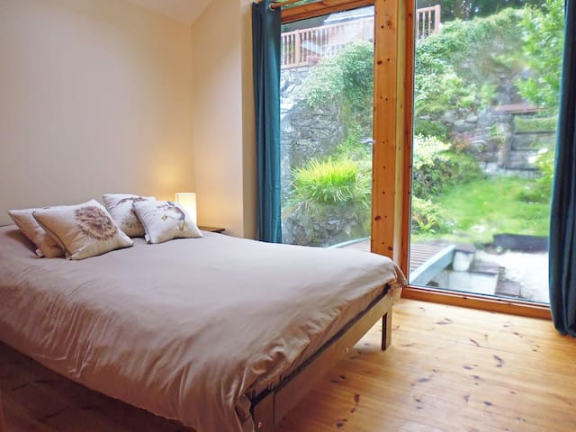 Bedroom 2 at the rear of the cottage features a glass wall overlooking the garden with a patio door providing direct access to the garden and the elevated decked terrace.
