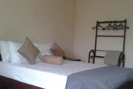 A large bed room with a queen size bed and AC