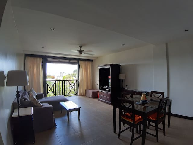 Large living, dining area, with full size sliding doors overlooking the pool