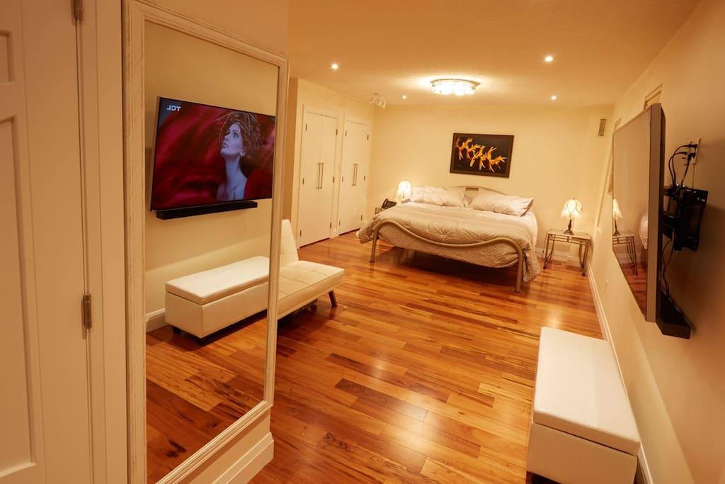 "Master Bedroom and 65"" 4K HDTV."