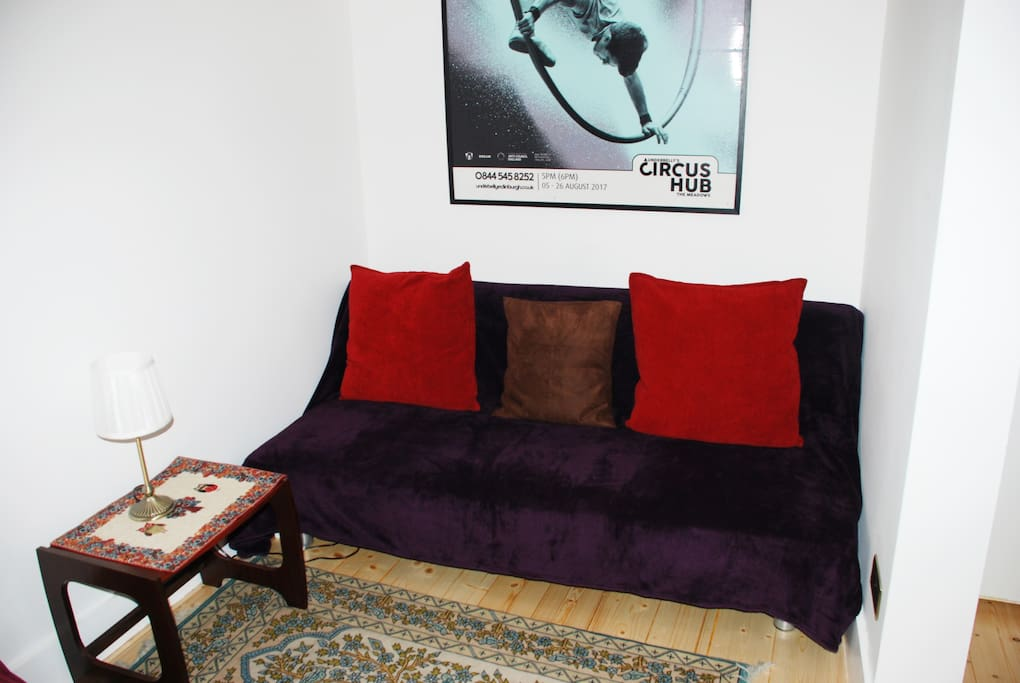 The living room sofa with an Edinburgh Festival poster above it