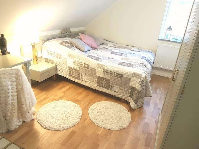 Mid size bedroom utrustat med dubbelsäng, skrivbord och dubbelgarderob