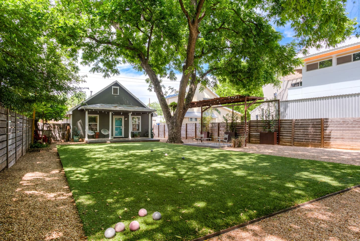 large front yard with steel framed turf, situated under a 100 yr old pecan tree that provides shade and cooler temps. Play bocce ball or simply lounge in the enormous front yard. Tons of parking on premises and on the street. Access via streetside or alley.
