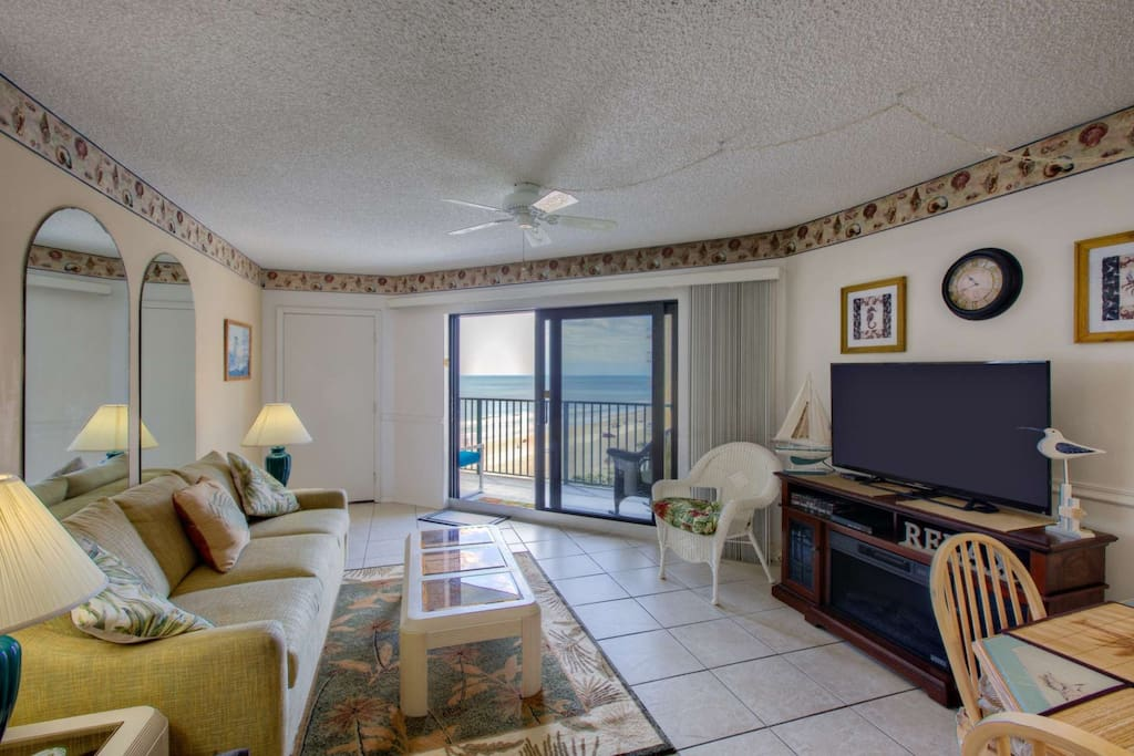 Living space with flat screen TV and easy access to it large balcony with views of the ocean and the ICW.
