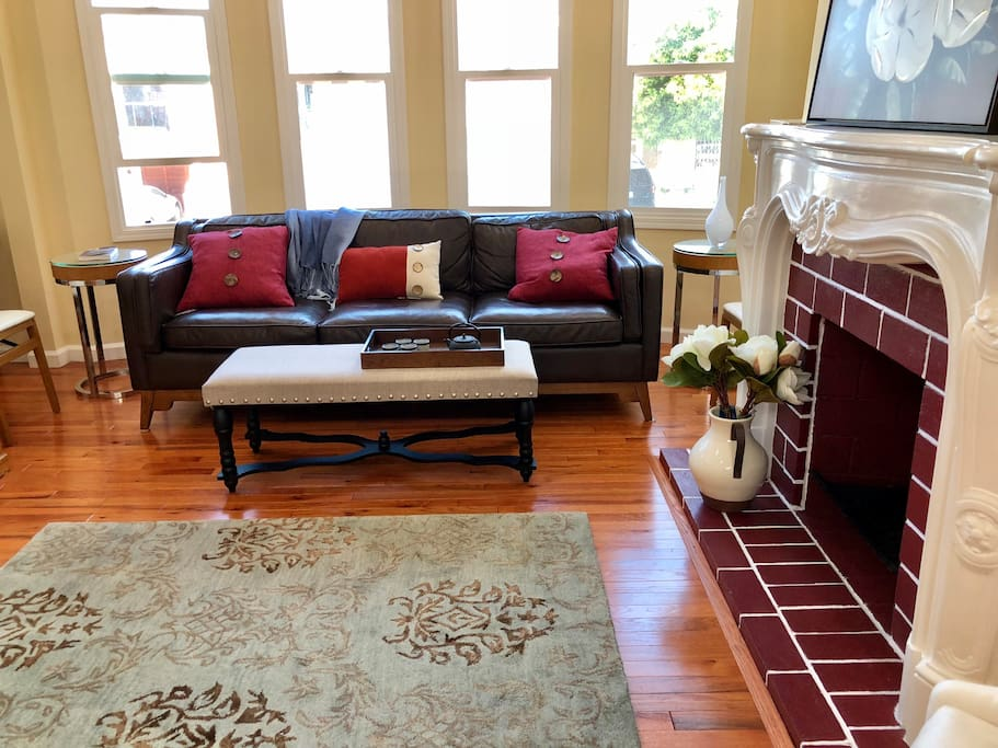 Designer Article leather sofa set against dramatic bay windows.