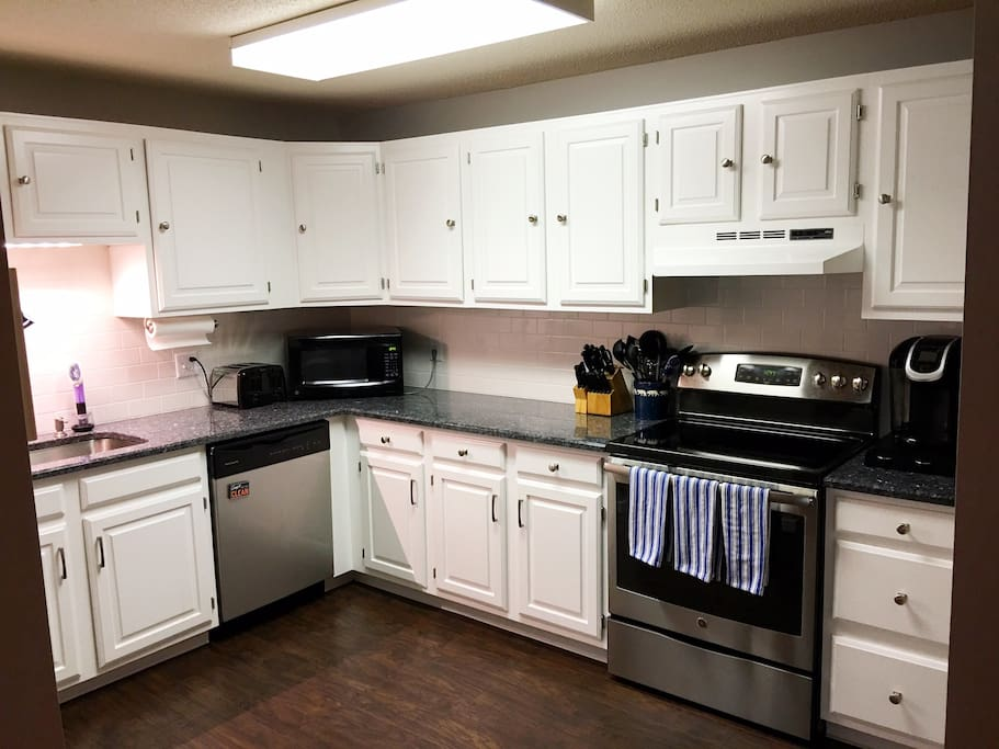 Modern, updated full kitchen with granite countertops, subway tile backsplash, brand new laminate flooring. Full size refrigerator is to the left of this photo.