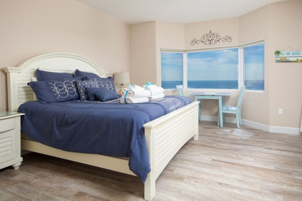 Palatial Master Suite with King bed, bay windows and seating area and wood tile floors