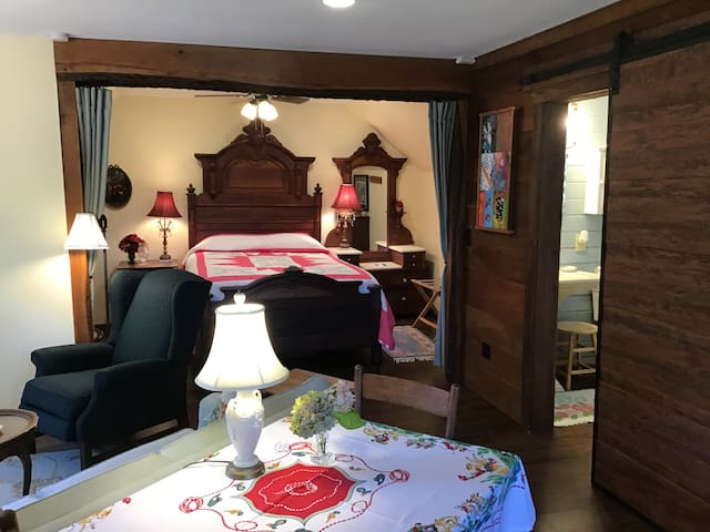 A cozy bedroom with a queen bed adjoins the living room along with a private bathroom.  A dining table and chairs to eat or work are also provided.