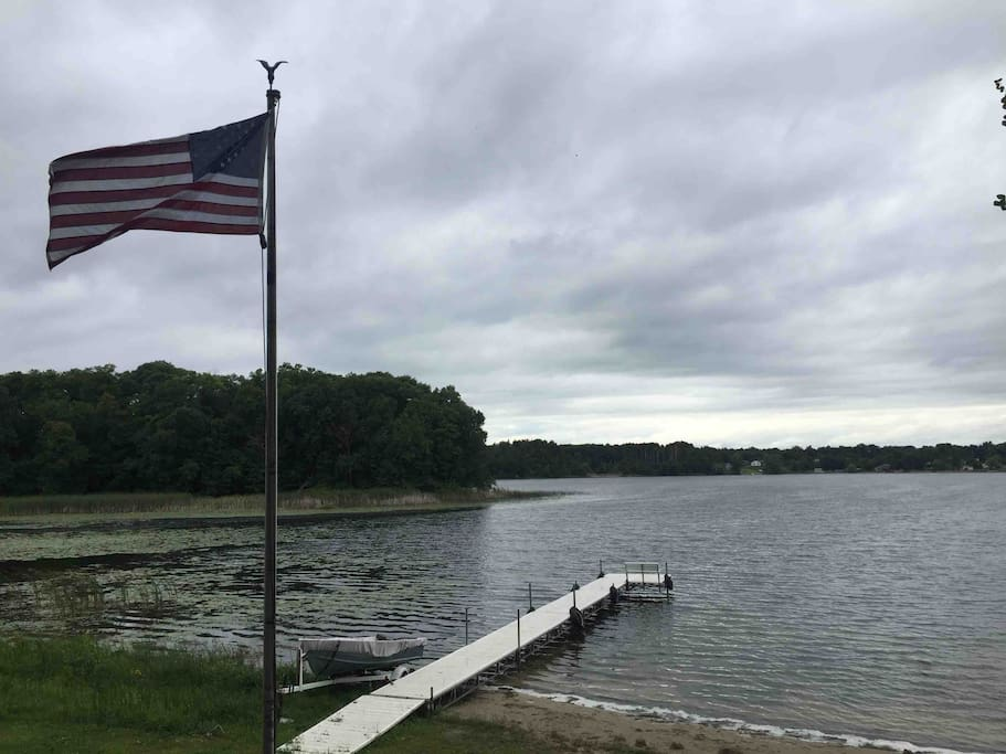 Dock and lakeshore on a cloudy day.   Large back yard with trees provides some privacy and room to play.