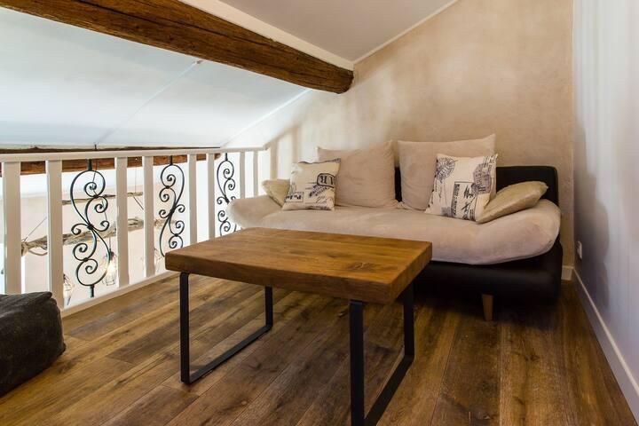 Salon mezzanine au-dessus de la cuisine avec canapé convertible