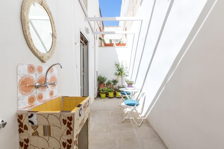 Veranda con piccolo giardino di piante aromatiche, tavolino con due sedie, sdraio, lavandino, specchio, doccia esterna e fili per il bucato