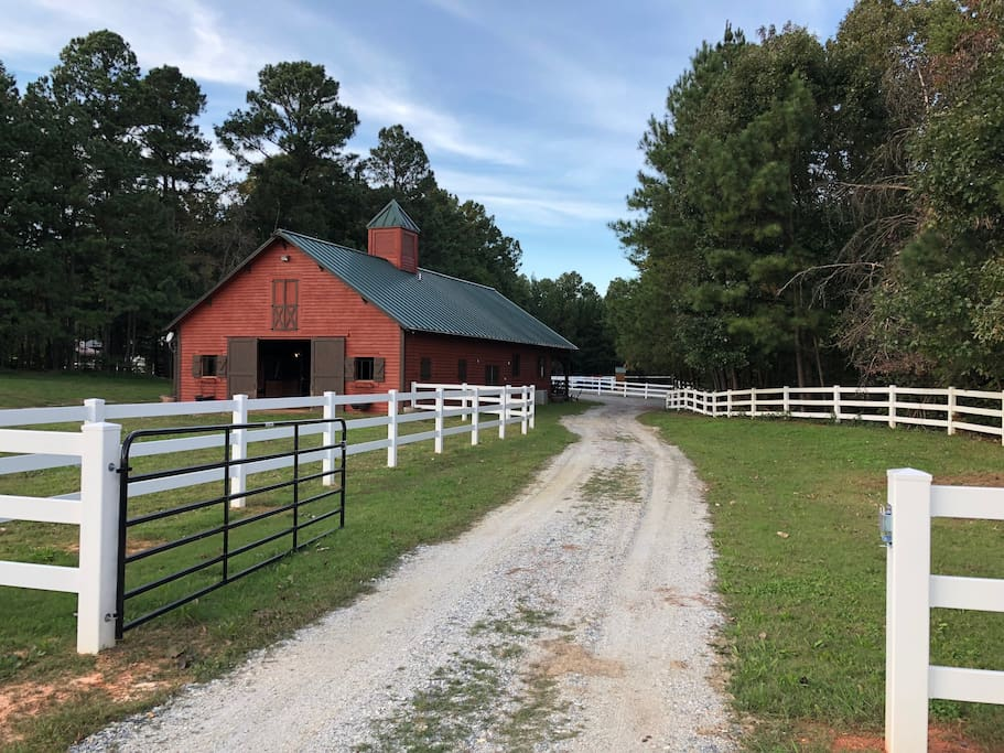 Gated driveway to barn with parking lot off front porch