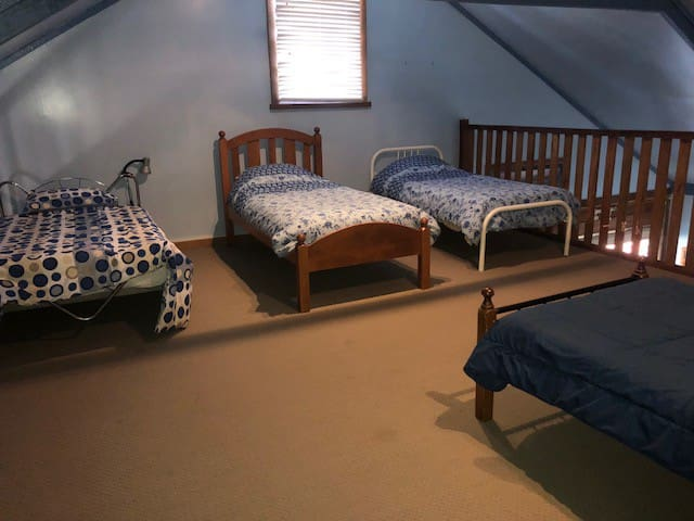 Upstairs loft area which can sleep 4 in single beds - with ceiling fan.