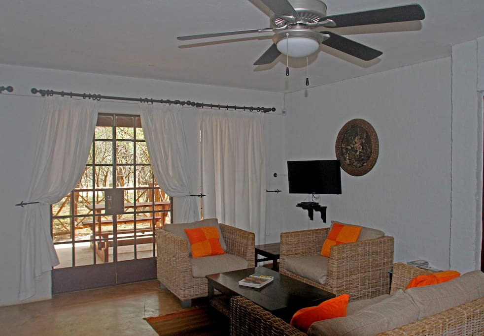 The living area looks out on to the patio and and the bushveld  beyond.