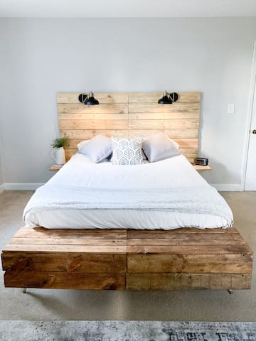 Rustic-style queen bed with fresh linen sheets and built-in bench and dimmable scone lights