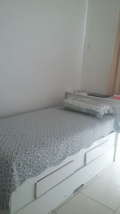 Quarto com cama auxiliar e ventilador de teto.