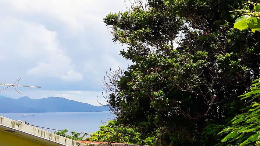 Vue sur le sud de la Martinique depuis la terrasse à l'arrière de la maison. Vous y trouverez la machine à laver, l'étendoir à linge et une petite table-bar idéale pour prendre son café ou son thé le matin !