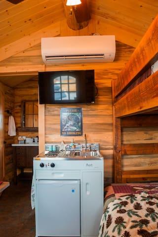 The kitchen (sink, 2- burner stove, 3.2 cu. ft. Refrigerator) satellite TV, heat pump/air conditioning, and bunk bed (twin over full/double) in the Bunkhouse Cabin.