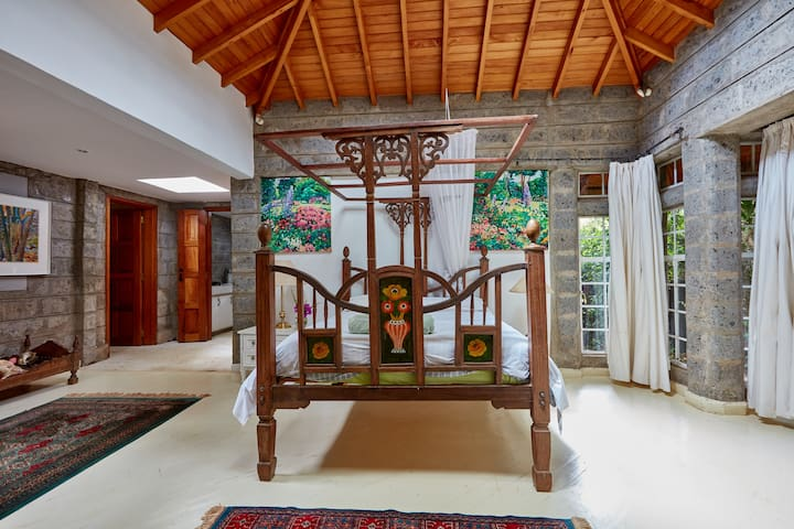 The traditional Swahili bed is placed across the bedroom fireplace