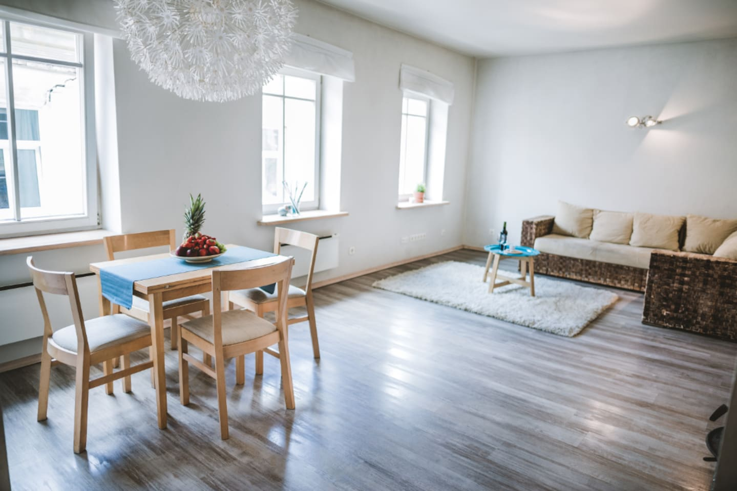 Spacious and bright common area with a dining table and a cozy corner sofa