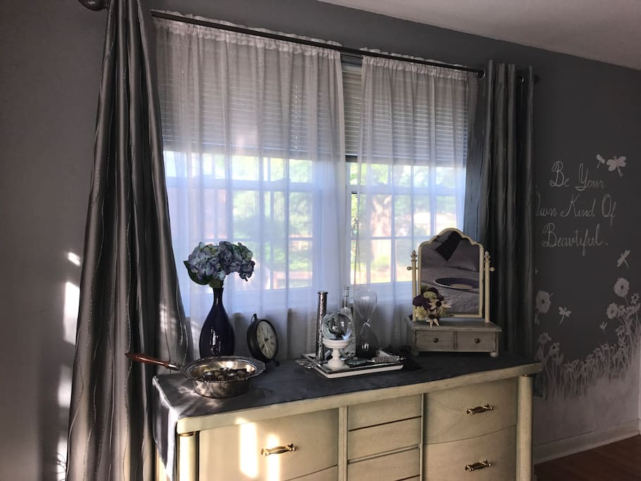 Be your own kind of beautiful! Gorgeous double window with curtains and blinds, framing a dresser for you to use.
