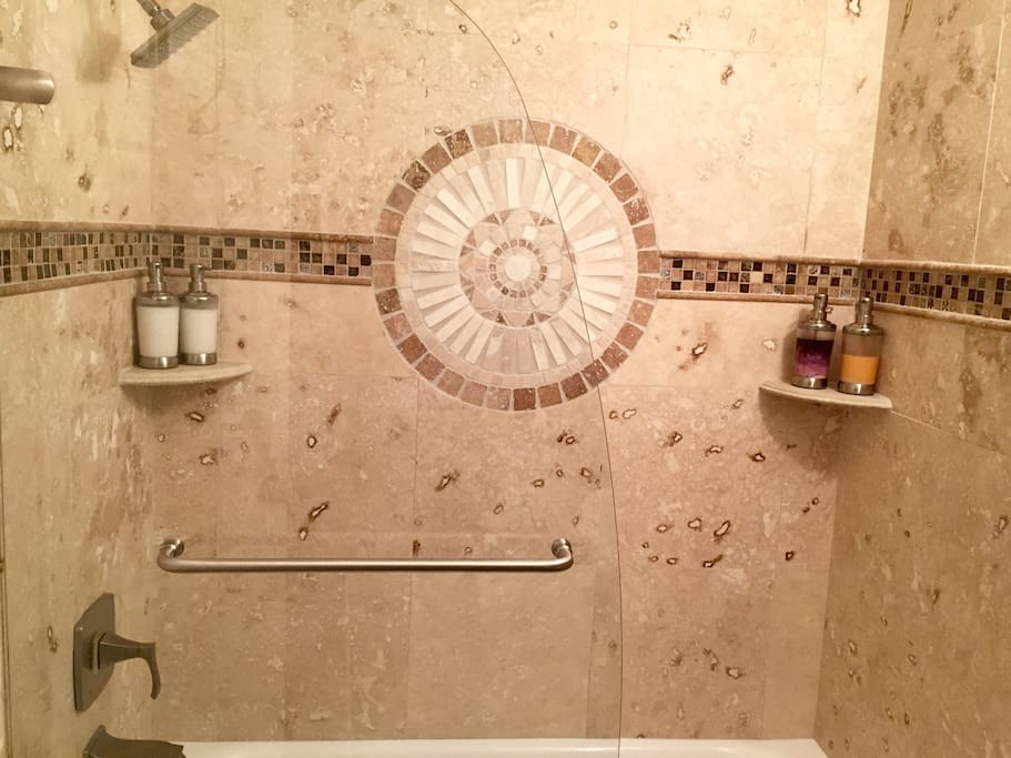 Travertine and frameless glass doors. Includes soaps