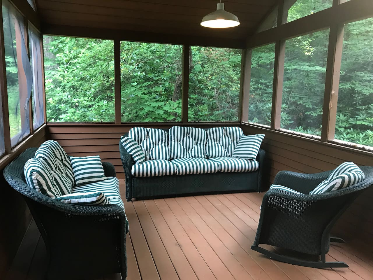 Screened porch with comfy couches and rocking chair.