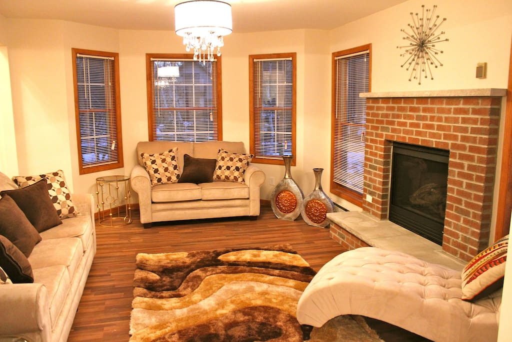 Beautiful relaxing room with red brick gas fireplace, couches, chaise lounge chair and lots of windows