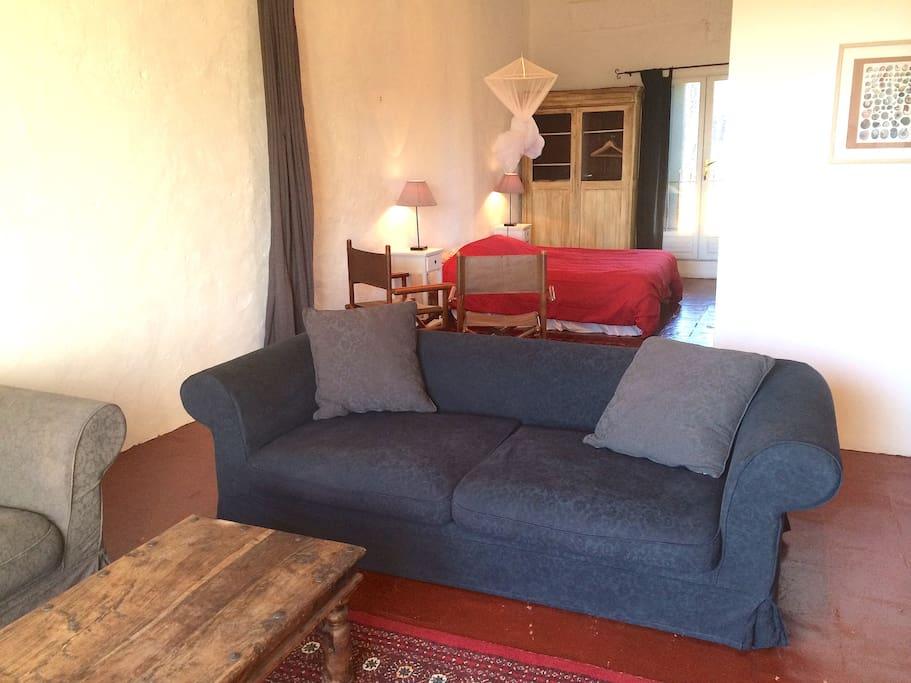 canapé et lit avec rideaux de séparation