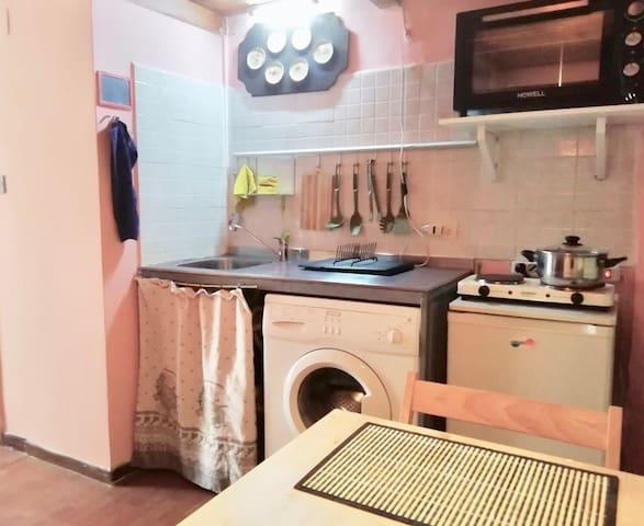 Kitchen corner with washing machine, fridge and oven.