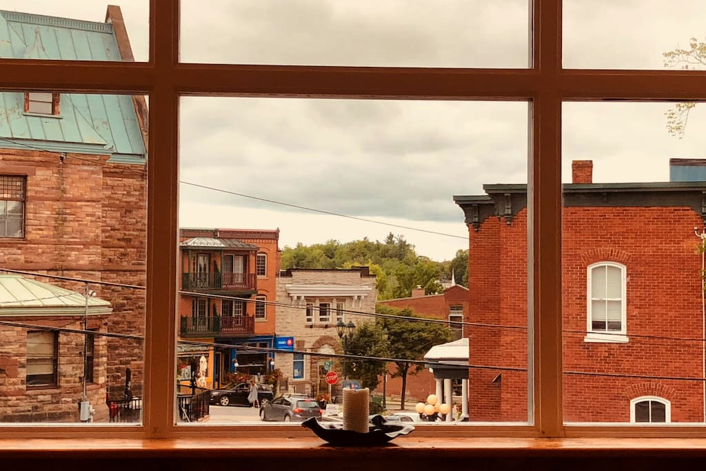 """Our """"Town-aquarium"""" view overlooks heritage downtown Almonte. Watch the sky, people-watch, marvel at the cirque-du-soleil high-wire squirrels ... or dream a little dream on the couch where this photo was taken."""