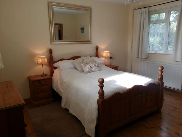 spacious double bedroom with bedside tables, lamps and soft rugs. Large wardrobe and chest of drawers