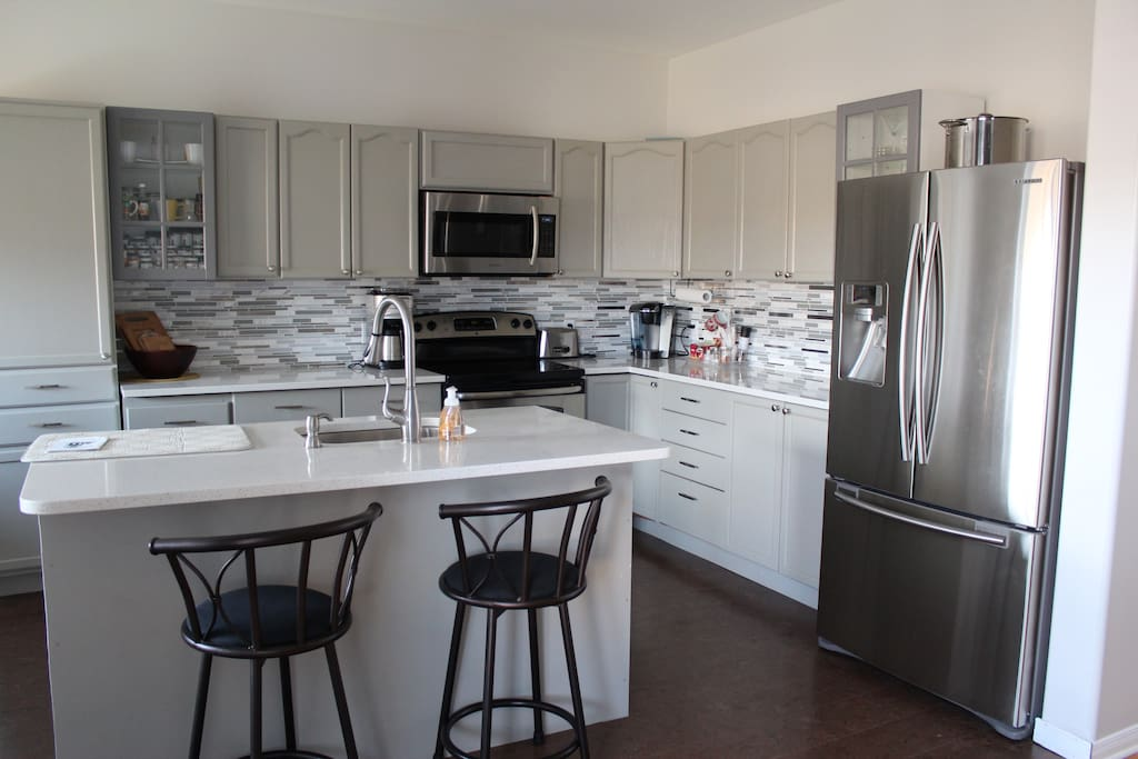 Bright and spacious! Fully stocked eat-in kitchen plus island with full amenities: fridge, freezer, stove microwave, dishwasher, coffee pot/grinder, milk steamer, Keurig, teapot blender, dishes, utensils, pots/pans, mugs/glasses, filtered cold water/ice maker, Everything plus the kitchen sink!