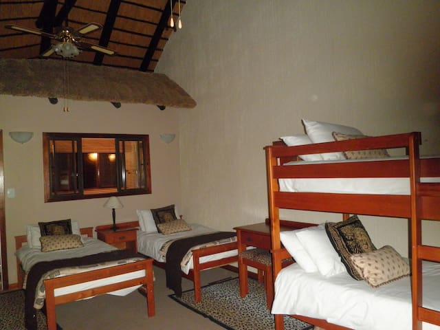 Loft room with twin beds and bunk bed. Modern bathroom and balcony overlooking wooded garden