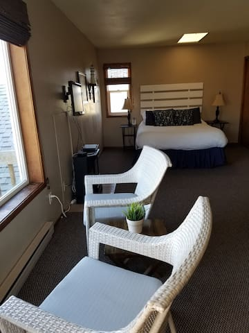 queen bed and chairs to sit and look at the ocean. Jacuzzi to the right.