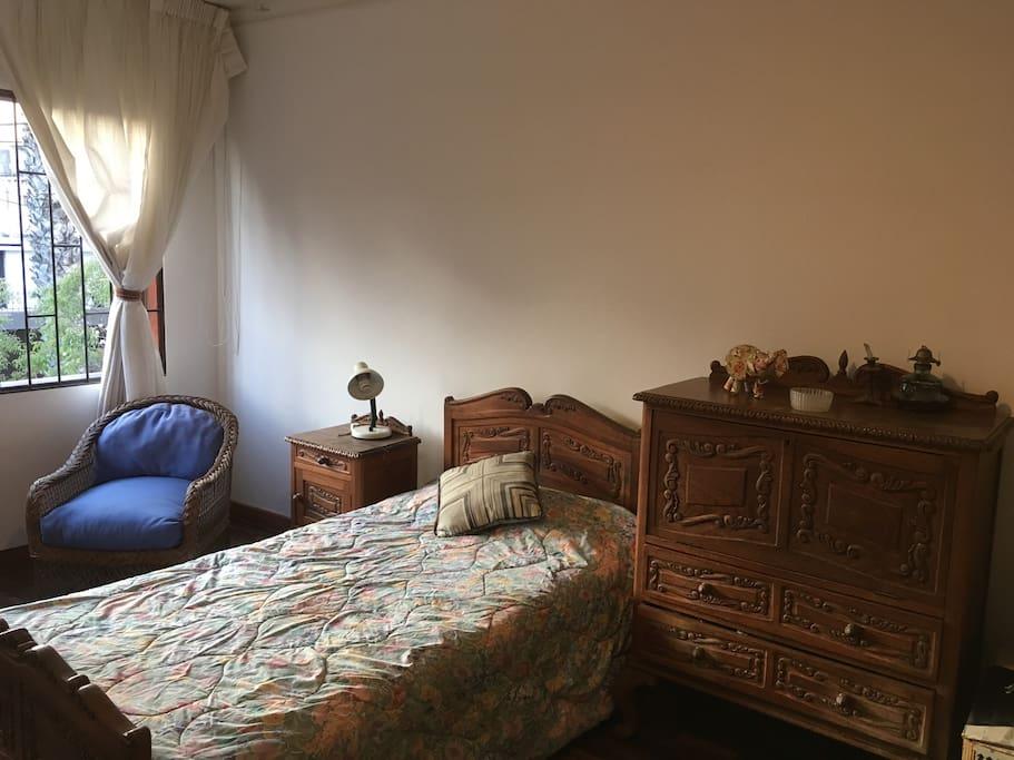 Amplia habitacion con cam de una plaza y fino mobiliaria en madera tallada. Amplios closets. Listo vista a una serena y linda calle arboleada