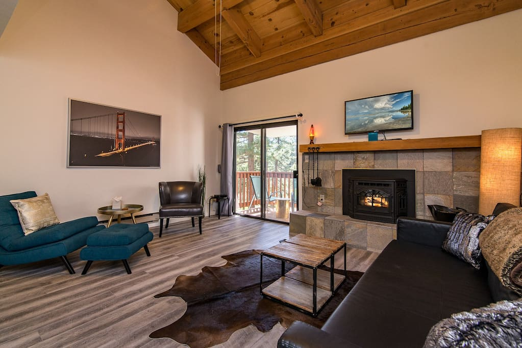 The living room features exposed-beam vaulted ceilings, a fireplace and a couch that converts into a sleeper sofa.