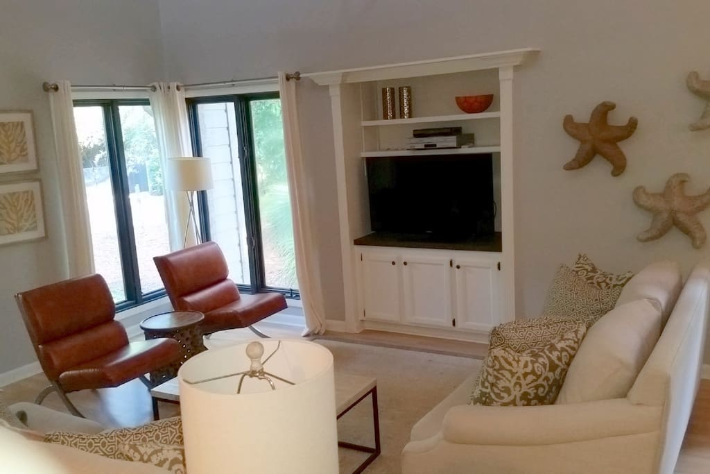 Large, professionally decorated living room has HDTV, comfortable furnishings, and beautiful views.
