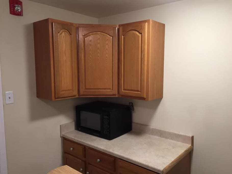 Microwave and cabinets with dishes and essentials.
